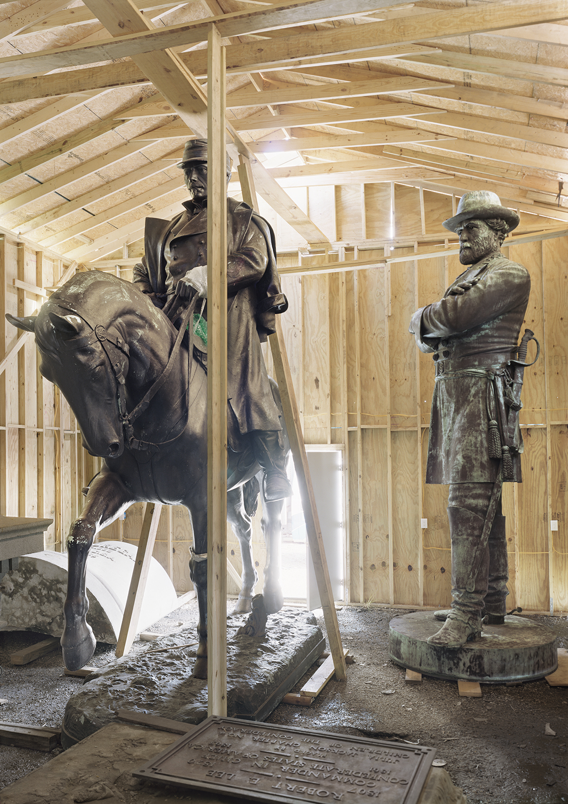 A wooden structure encloses two bronze monuments of Civil War figures